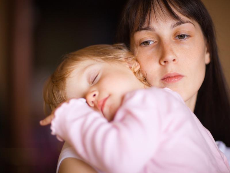 Sleepy little child with mom - shallow DOF, focus on woman's eyes